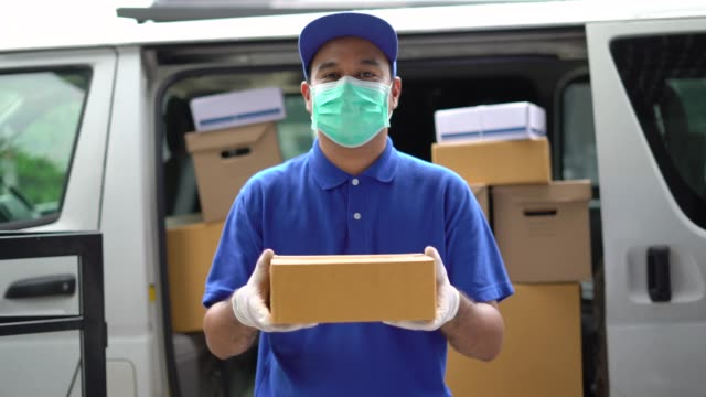 Corona Virus concept, Blue Delivery handsome asian man holding parcel cardboard box with protection mask and medical rubber gloves standing in front of the van. 4k resolution and slow motion shot.