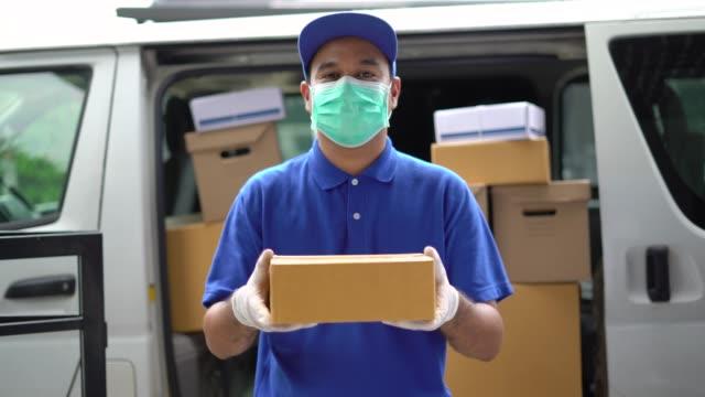 冠狀病毒的概念,藍色交付英俊的亞洲男子拿著包裹紙板箱與保護面具和醫療橡膠手套站在麵包車前面。4k 解析度和慢動作拍攝。 - postal worker 個影片檔及 b 捲影像
