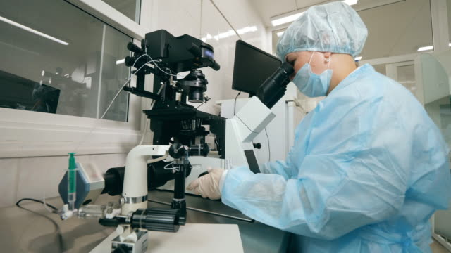 Coronavirus epidemia, virus vaccine concept. Female expert is operating a microscope in the lab facility video
