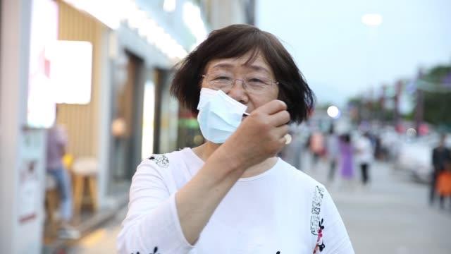 Coronavirus is over!Senior asian woman take off protective mask
