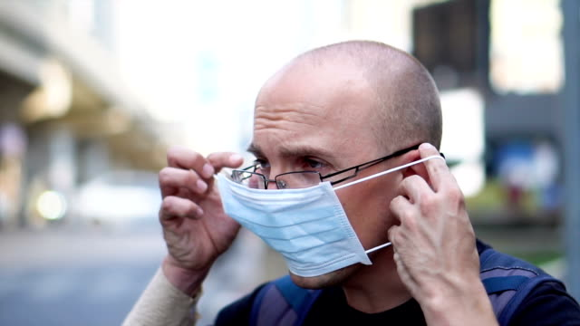 coronavirus outbreak - infected man coughing and putting on surgical mask - face mask stock videos & royalty-free footage