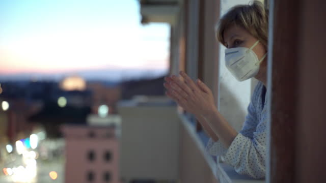 coronavirus pandemic in the world, people staying at home, quarantine concept. woman in protective mask looking out of the window and clapping hands supporting national flash mob in italy, applauding medical staff who fighting against coronavirus - balcone video stock e b–roll