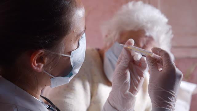 karantina sırasında coronavirus koruması. kadın doktor evinde yaşlı bir kadına tıbbi muayene yapıyor. sıcaklığı ölçüyor. - hemşire tıbbi personel stok videoları ve detay görüntü çekimi