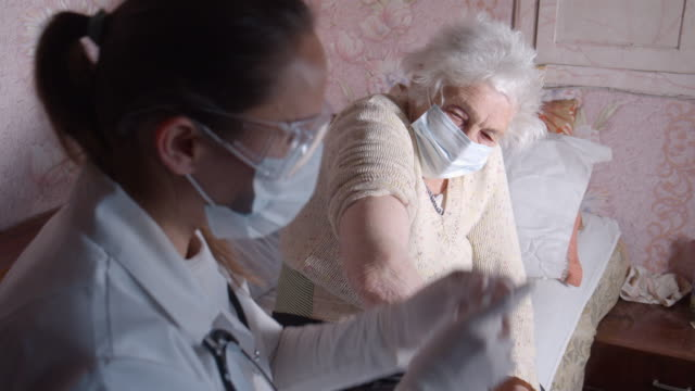 coronavirus protection during the quarantine. female doctor giving vaccination to a senior woman at her home. - vaccine filmów i materiałów b-roll