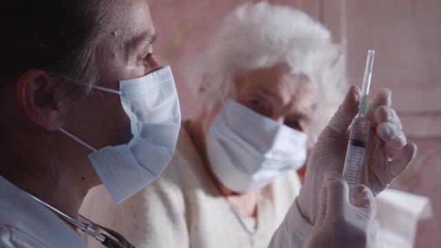 coronavirus skydd under karantänen. kvinnlig läkare som vaccinerar en äldre kvinna i sitt hem. - corona vaccine bildbanksvideor och videomaterial från bakom kulisserna