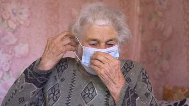 coronavirus protection. senior woman wearing mask to avoid infectious diseases. - mask стоковые видео и кадры b-roll