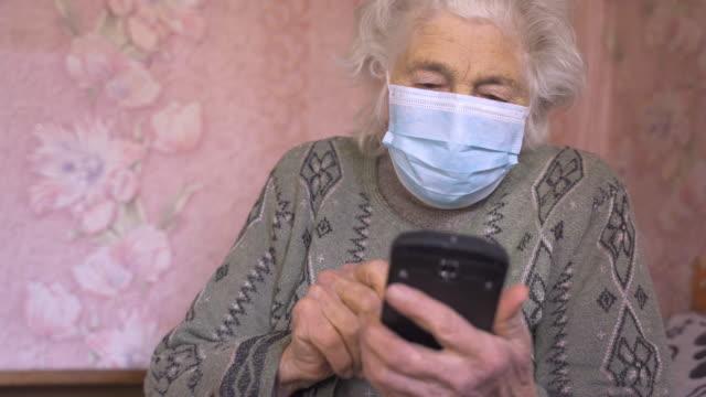 protezione dal coronavirus. donna anziana che indossa la maschera per evitare malattie infettive. - donne anziane video stock e b–roll