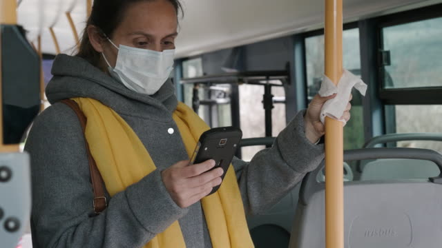 Coronavirus protection. Woman with a protective mask to avoid infectious diseases, surfing the internet while  in the bus shuttle. Woman with a protection mask using phone and getting off the bus . bus stop stock videos & royalty-free footage