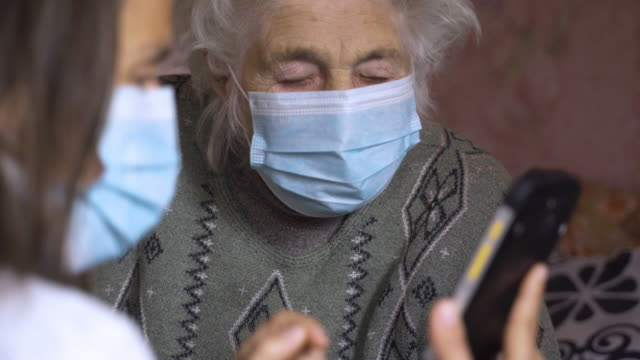 Coronavirus protection. Women wearing mask to avoid infectious diseases. Young woman with her grandmother, discussing the coronavirus. Both with protective masks on their face. Searching for information on the internet. looking for advice. granddaughter stock videos & royalty-free footage