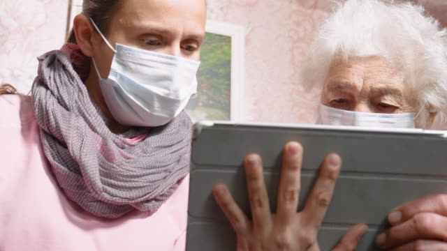 Coronavirus protection. Women wearing mask to avoid infectious diseases. Young woman with her grandmother, discussing the coronavirus. Both with protective masks on their face. Searching for information on the internet. looking for advice. stay home stock videos & royalty-free footage
