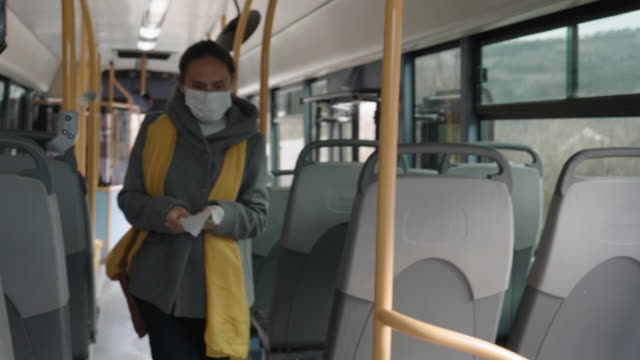 Coronavirus protection. Worried woman with a protective mask on her face traveling with bus after work. Getting the bus after work. bus stop stock videos & royalty-free footage