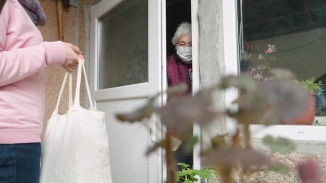coronavirus protection. young adult doing food deliveries, groceries and supplies to a senior woman. illness prevention. people with protective mask on their faces. - mask filmów i materiałów b-roll