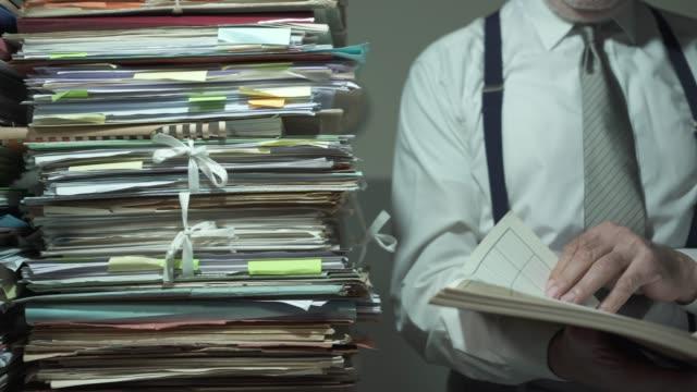 vidéos et rushes de homme d'affaires d'entreprise et piles de paperasse - dossier document