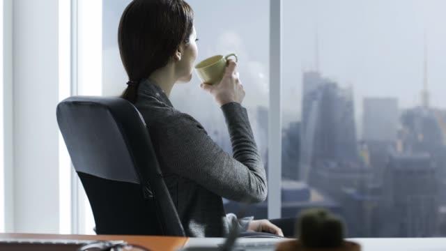 企業女商人在辦公室裡喝咖啡休息 - 看窗外 個影片檔及 b 捲影像