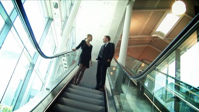 Corporate couple on escalator HD video