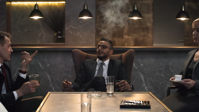 corporate executive talking with colleagues and smoking cigar - sigaro video stock e b–roll