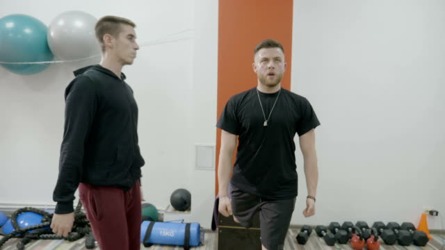 Corporate guy motivated to stay fit and healthy sweating while doing weight loss lunges with his personal trainer video