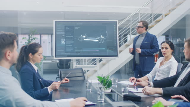corporate meeting room: chief engineer uses digital interactive whiteboard for presentation of electric car concept to a board of executives and investors. screen shows 3d cad animation of a vehicle - veicolo a motore video stock e b–roll