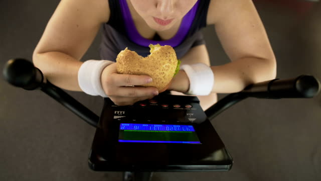 Corpulent female eating fatty burger while riding stationary bike, fast food Corpulent female eating fatty burger while riding stationary bike, fast food laziness stock videos & royalty-free footage