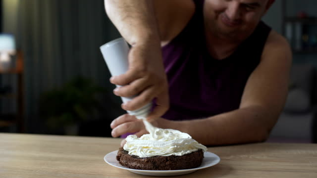 Corpulent man decorating chocolate cake with whipped cream, unhealthy food video