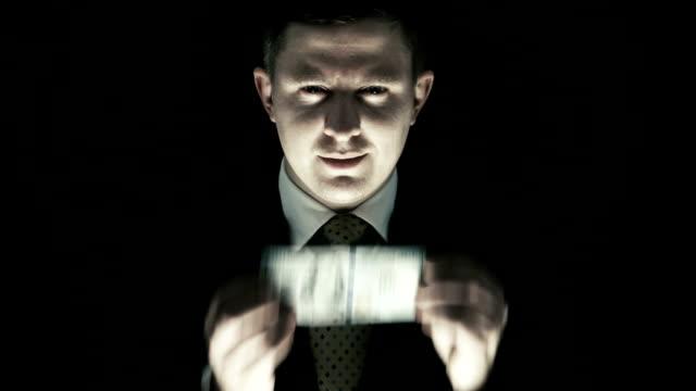 la corruzione, persona con volto spaventoso a una banconota da cento dollari di bocca - avidità video stock e b–roll