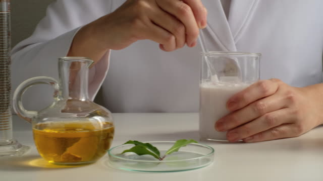 cosmetic and skincare making in the laboratory with natural ingredient. Scientist stirs the cream an lotion int he beaker.