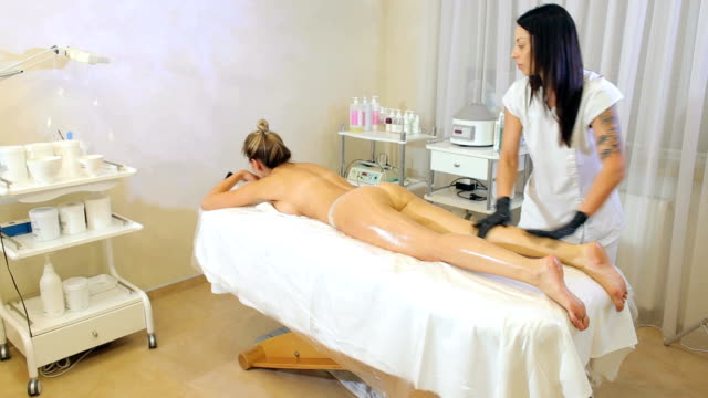 Cosmetic massage procedure, scrubbing skin and body wraps at a Spa salon. A young girl beautician does a massage to a woman, she rubs her legs with oil. Anti-cellulite massage in the spa salon. beauty salon stock videos & royalty-free footage