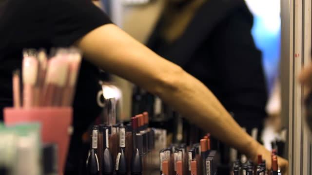 sprzedawca sklepu kosmetycznego oferujący produkty do makijażu, biznes, wystawę urody - kosmetyczka praca w salonie piękności filmów i materiałów b-roll