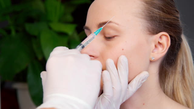Cosmetic treatment with botox injection in a clinic video