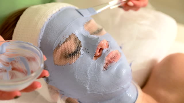 cosmetician applying facial mask to the face of young woman in spa salon - facial stock videos & royalty-free footage