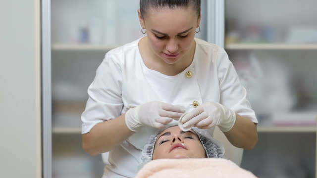 Cosmetician cleaning woman`s face with cotton pads at beauty salon video