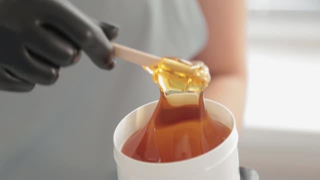 kosmetyczka pobiera pastę cukrową ze słoika. shugaring. wyklej cukier z pojemnika szpatułką. pasta cukrowa do cukrowania. cukrowanie w salonie kosmetycznym - depilacja filmów i materiałów b-roll