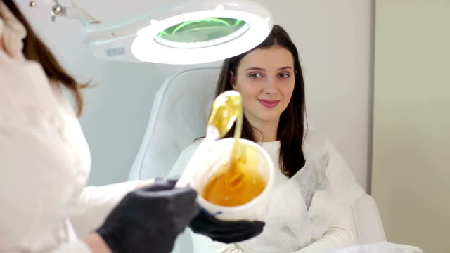 cosmetician takes the sugar paste from the jar. shugaring. - miele dolci video stock e b–roll