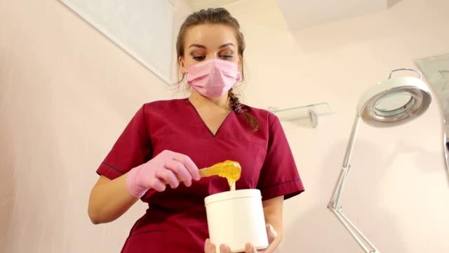 cosmetician takes the sugar paste from the jar. sugaring in beauty salon. - kosmetyczka praca w salonie piękności filmów i materiałów b-roll