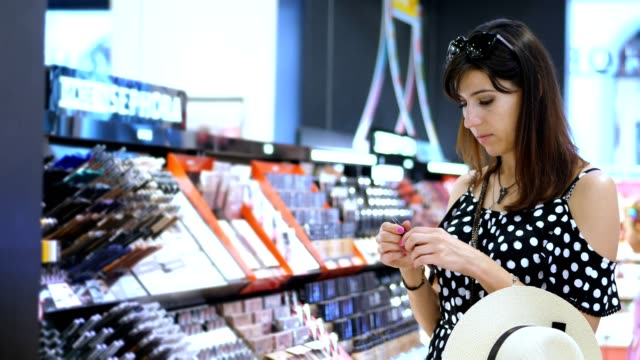 cosmetics shop, beautiful brunette, a woman carefully considers, chooses cosmetic products. Portrait of young smiling female brunette shopping in beauty store - vídeo