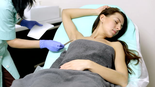 cosmetologist applies gel to armpits of patient before epilation procedure video