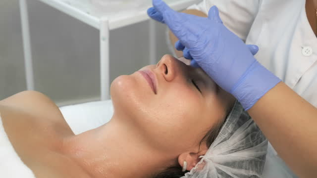 Cosmetologist applying gel with hyaluronic acid on woman face, closeup view. video