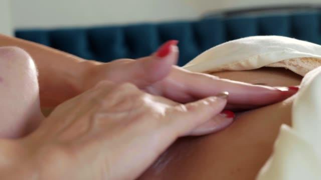 美容師は若い美しい女性の顔クリーム マスクを適用します。 ビデオ