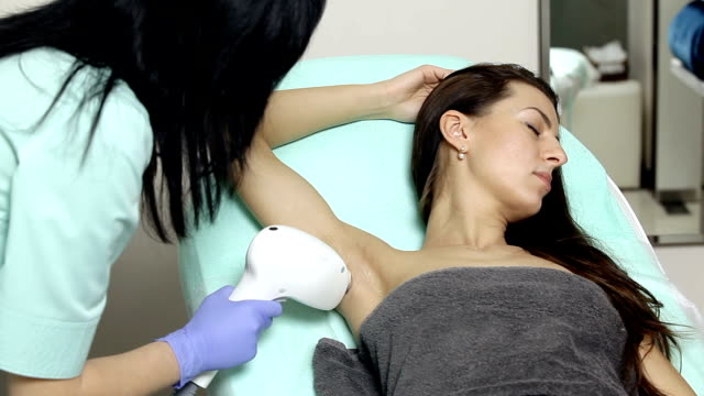 cosmetologist does laser hair removal of armpits of patient. Epilation procedure video