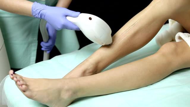 cosmetologist does laser hair removal on legs of patient. epilation procedure - depilacja filmów i materiałów b-roll