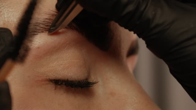 stockvideo's en b-roll-footage met schoonheidsspecialist hand trekt wenkbrauwen - eyeliner