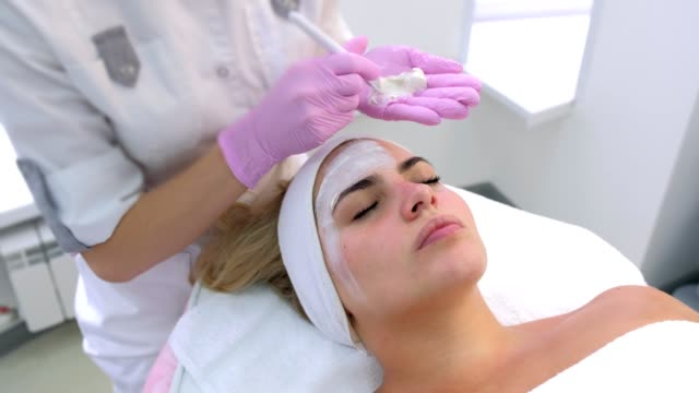 Cosmetologist is applying white mask on woman client face in beauty clinic. video