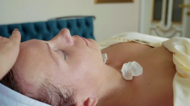 Cosmetologist is cleaning woman's face by cotton sponge at spa salon video