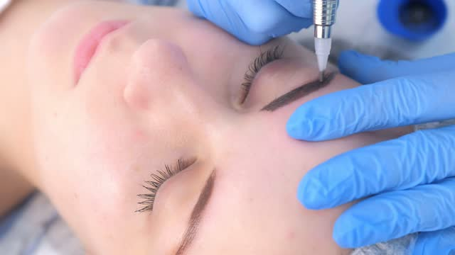Cosmetologist making eyebrows microblading procedure in beauty salon for girl. video