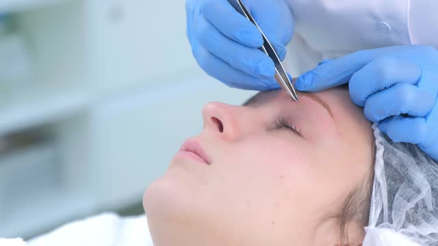 Cosmetologist plucks out hair on eyebrows with tweezers for woman, face closeup. video