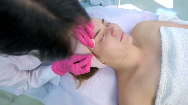 Cosmetologist poking acne on woman's face using needle and wiping cotton pads. Cosmetologist is poking acne on woman's face using needle and wiping cotton pads. Mechanical cleaning of face at the beautician. Portrait of girl patient, side view. Doctor making treatment or cure. beautician stock videos & royalty-free footage