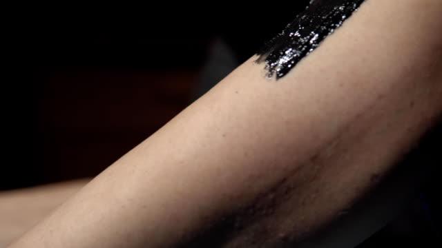 vídeos de stock e filmes b-roll de a cosmetologist removes hair from the legs of a young woman sugar paste . - puxar cabelos