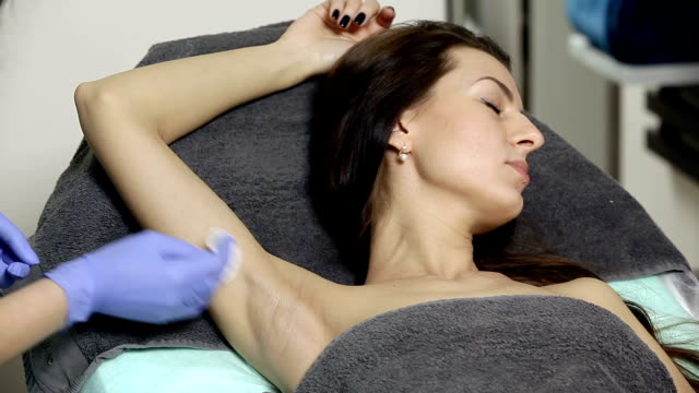 cosmetologist wipes patient's armpits with cotton sponge before procedure. disinfection video