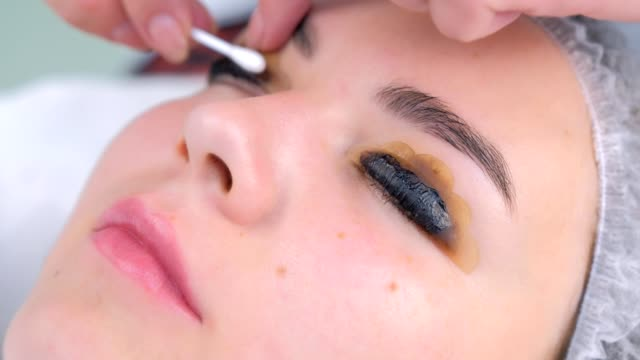Cosmetologist wiping solution from girl's lashes on painting procedure. Cosmetologist wiping solution from girl's lashes on painting procedure using cotton stick on lift lamination in clinic, woman face closeup. Beautician making lash lifting. Beauty industry concept. eyelash stock videos & royalty-free footage