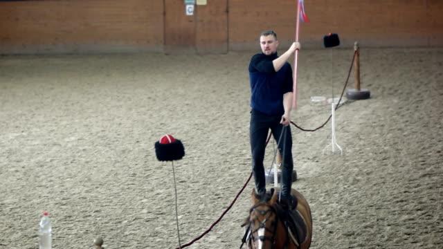 コサック若い男のアクロバットは馬の背中を行います - 動物に乗る点の映像素材/bロール